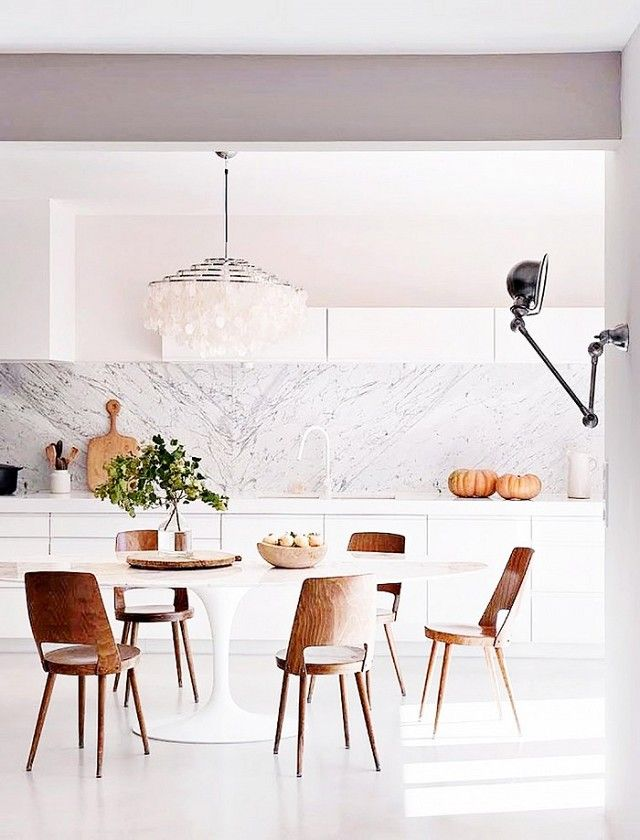 A Feminine Kitchen With Marble Backsplash, A Shell Chandelier, And Wooden  Chairs