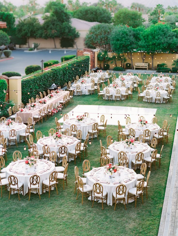 Above view of the entire wedding reception with round tables and oak Orion chairs. Head table with pink linens. White dance floor and market lights. Pink and ivory bold centerpieces with peonies and roses. Miramonte Resort reception on the Mesquite Lawn. Film photography by Cavin Elizabeth.