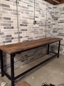 Painted concrete walls to look like brick. The table is made out of a work bench