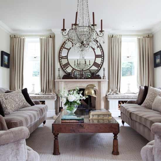 Elegant Sitting Room Striking Antique Objects Make A Statement In This Neutral Living The Fireplace Large Mirror And Impressive Chandelier Are
