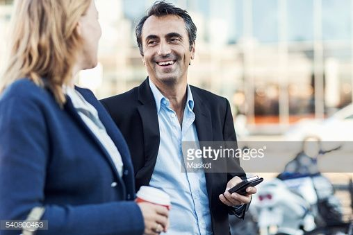 Stock Photo : Happy businessman talking to female colleague outdoors