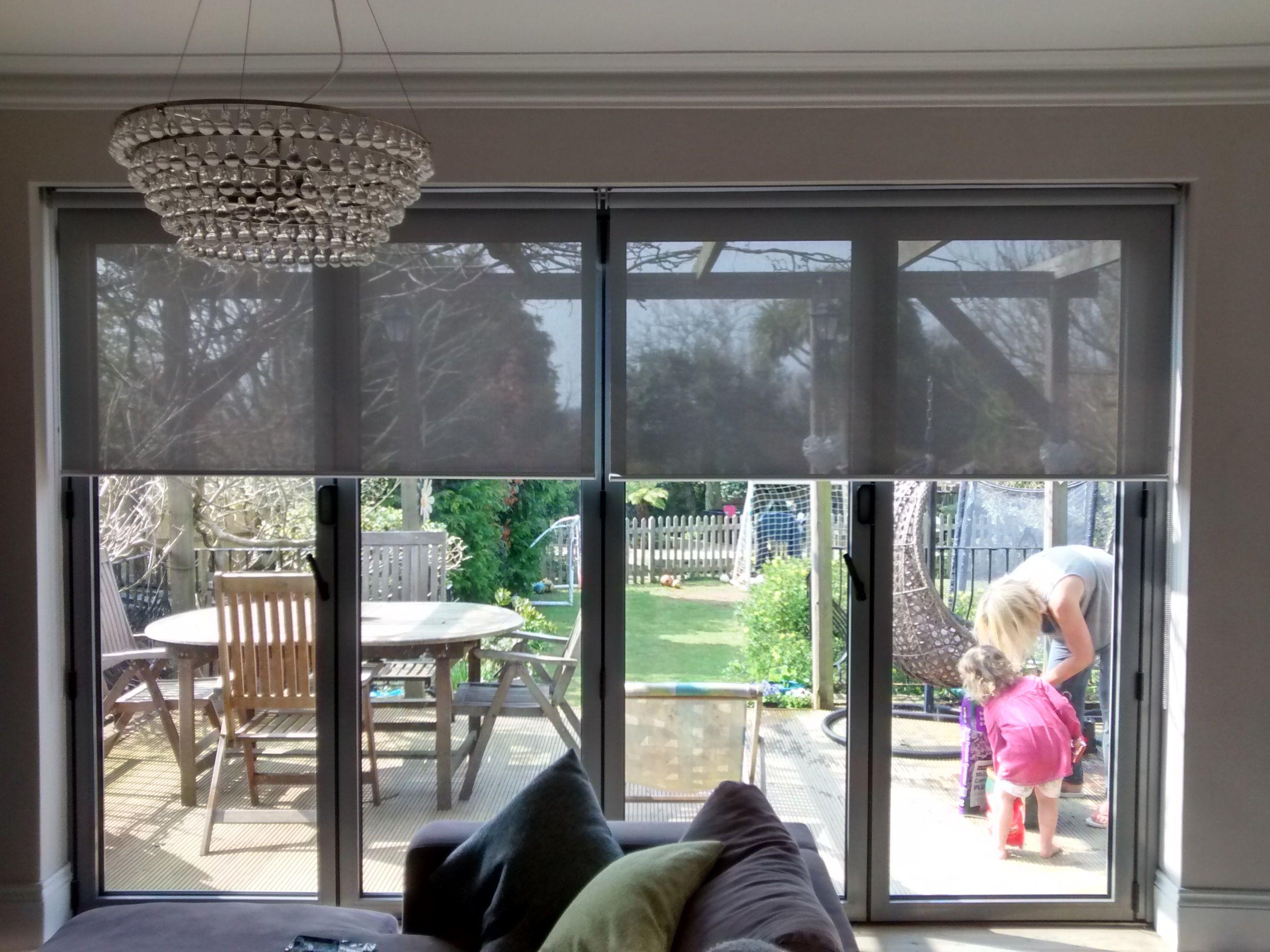 Sunscreen roller blinds over bifold doors in living room Supplied