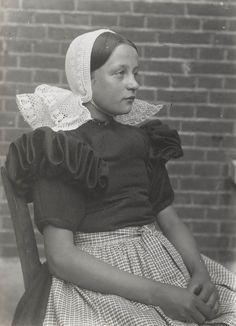 Meisje in Huizer streekdracht. Ze is tussen de 12 en de 16 jaar en draagt de daagse dracht. ze is gekleed in een jurk met pofmouwen, een 'lage schullek' ...