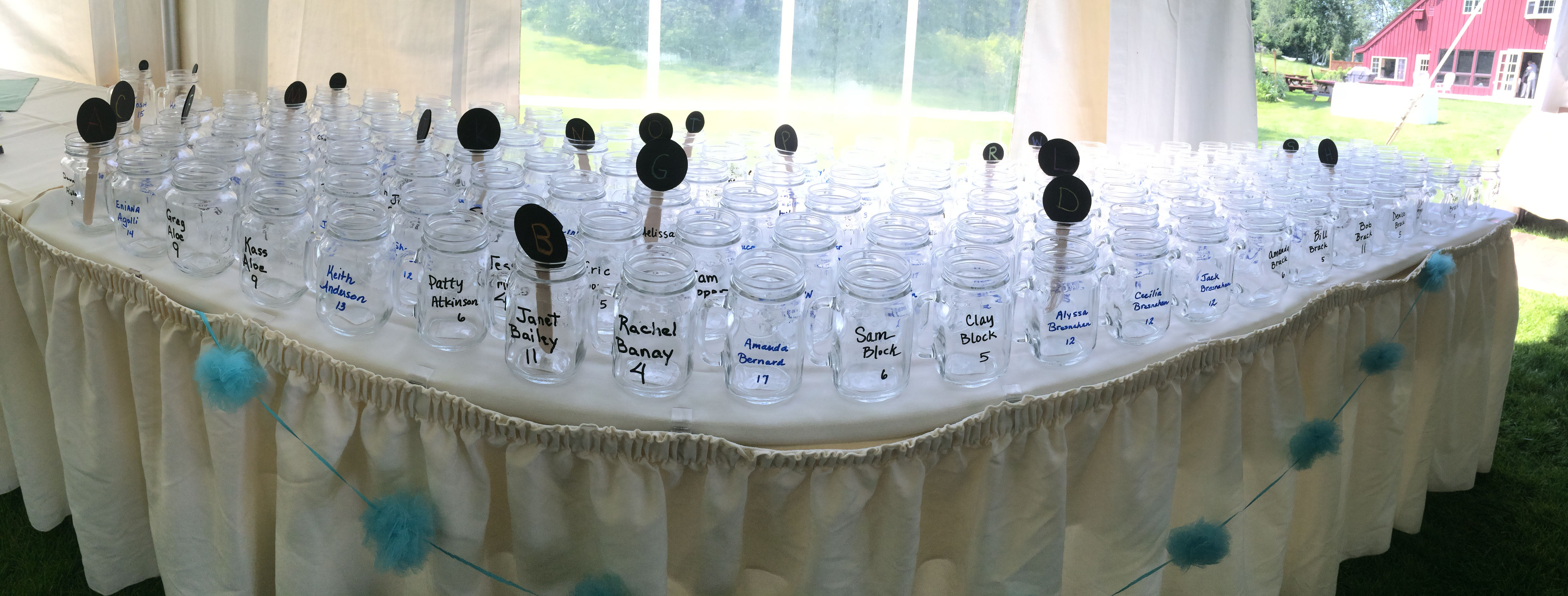 Mason jars are all the rage. Sharpie oil-based markers denote names and table numbers. Small signs help guests find their last name by alphabetical order.  Guests find their mugs to find their table, they reuse their mug all night (no wasting 10 plastic cups!) and take it home with them as a favor to remember your wedding day! #masonjar #masonjarwedding #weddingfavors #placecards