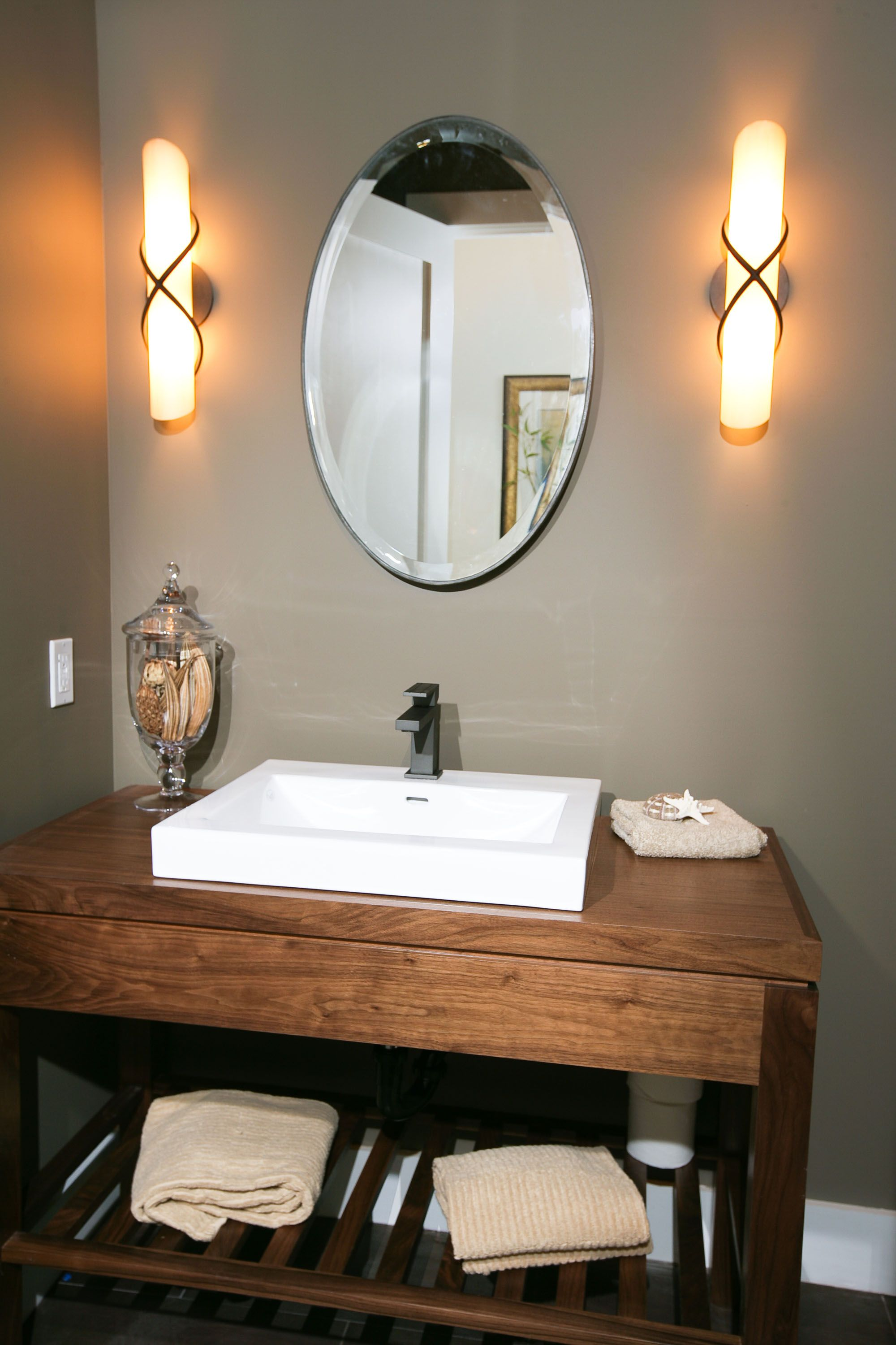 Powder Room featuring stained wood vanity with raised sink ...