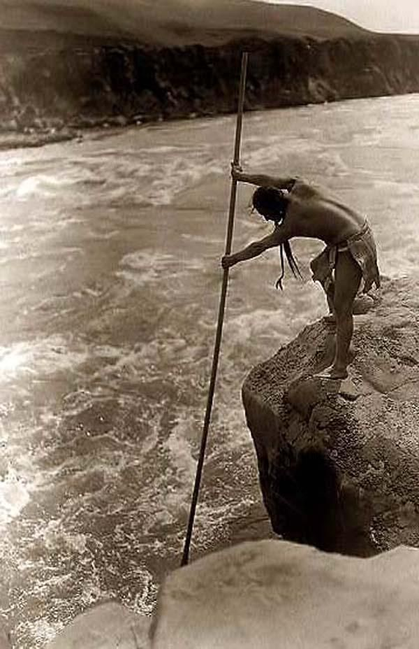 Here for your browsing pleasure is a nice photo of an Indian Fisherman. It was made in 1910 by Edward S. Curtis.    The illustration documents a Tlakluit Indian, standing on rock, fishing with dip net.    We have compiled this collection of photos mainly to serve as a vital educational resource. Contact curator@old-picture.com.