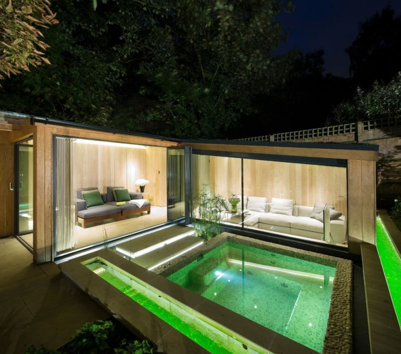 Maison de vacances dont lintérieur donne sur la piscine extérieure avec éclairage led vert