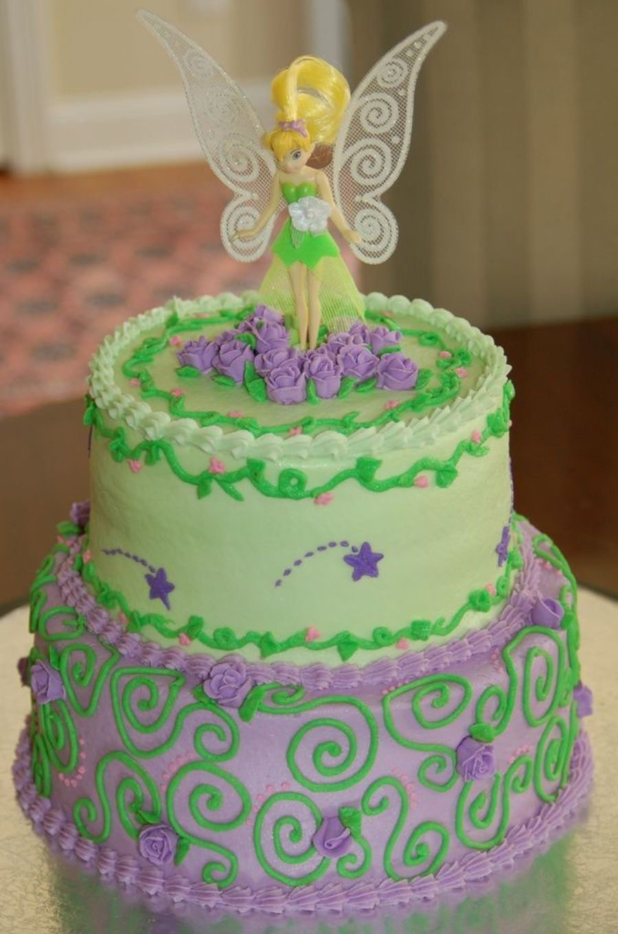 A twotiered baby shower cake w/ Tinkerbell theme. All