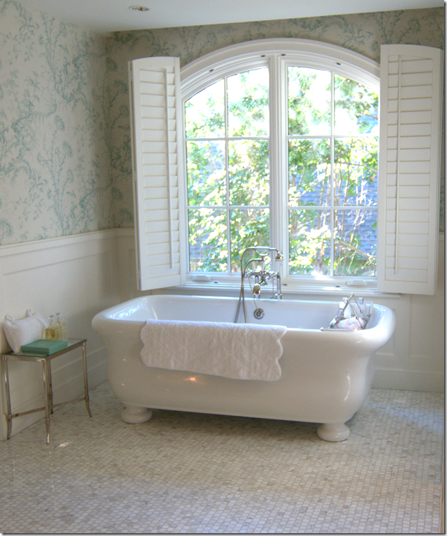 Freestanding Bath Sits Under An Arched Window.