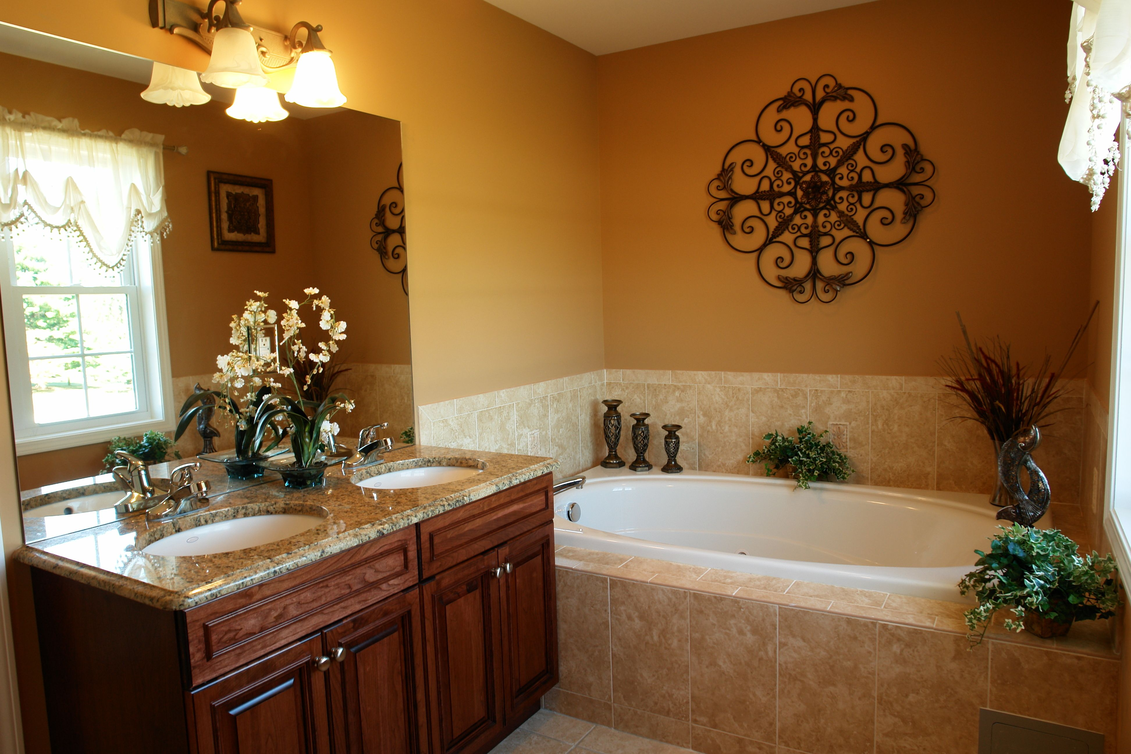 warm bathroom with dark cabinets and double sinks large jetted tub with tile work surrounding