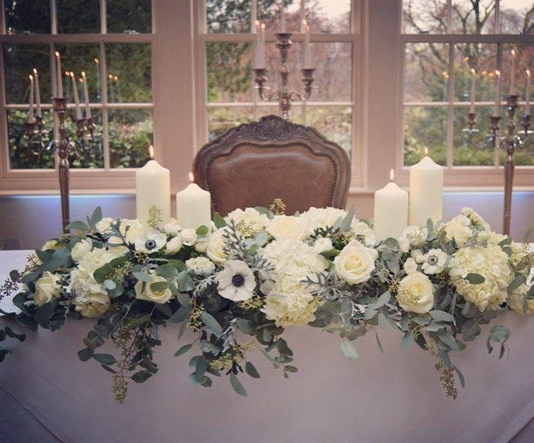 A Winter Wedding Top Table Arrangement Of White Anemones Ranunculus Roses And Silvery