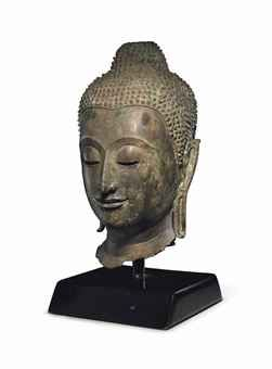 A bronze head of Buddha  Thailand, Ayutthaya, circa 16th century  Finely modeled with incised chin, bow-shaped mouth, elongated eyes and gently arching brows, flanked by pendulous earlobes, the hair in tight curls over the ushnisha 16¼ in. (41.3 cm.) high