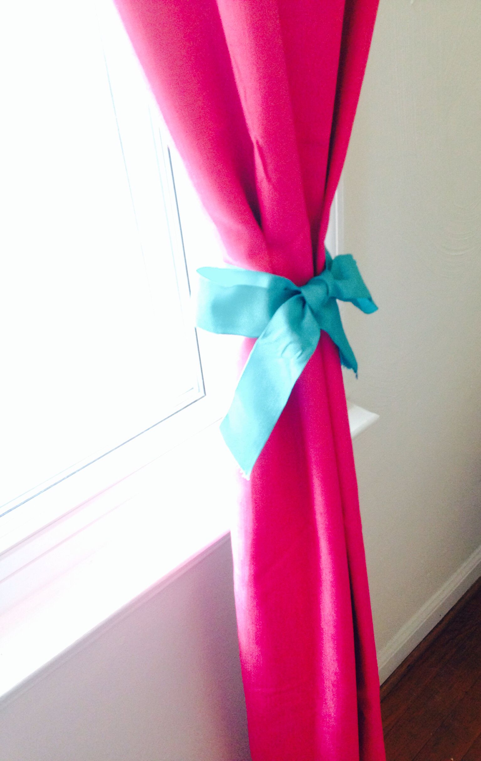 Details. Turquoise bows tied around fuchsia panel curtains