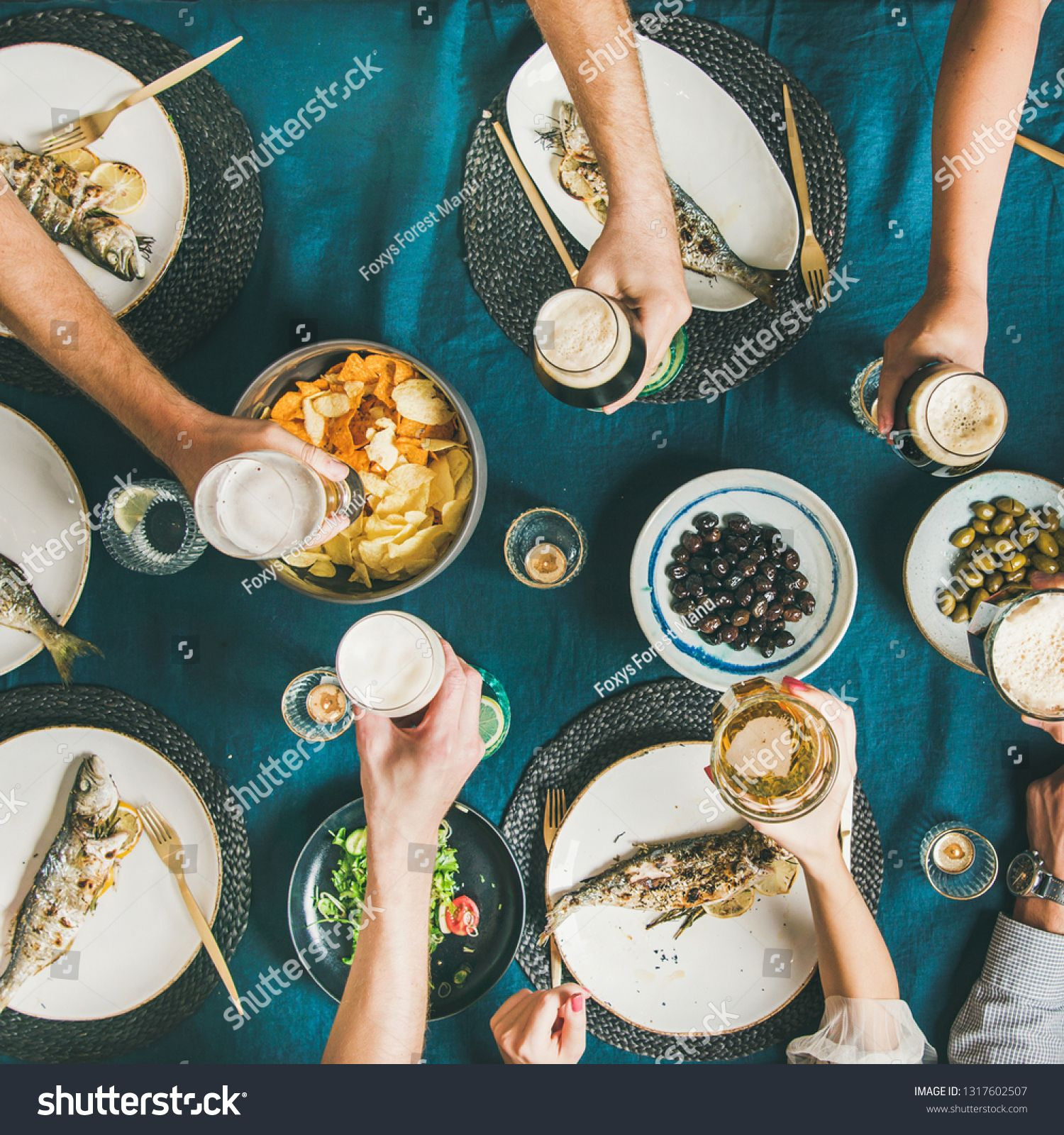 Fish, chips, beer party gathering of friends eating and drinking. Flat-lay of human hands, beer glasses, grilled sea bass fishes, vegetable salad, roasted potatoes and potato chips, square crop ,