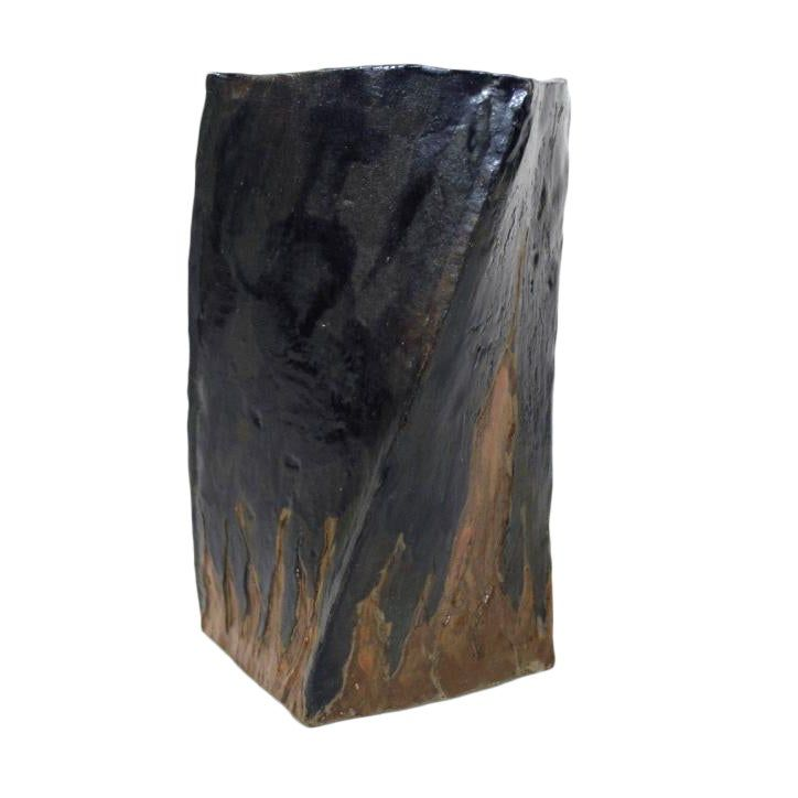 A deep blue hand built slab vase with flames along the bottom of two sides. In regular light is reads very dark blue but in brighter light, as pictured above, the glaze has a subtle marbled quality.A strong and graceful accent piece in any setting.