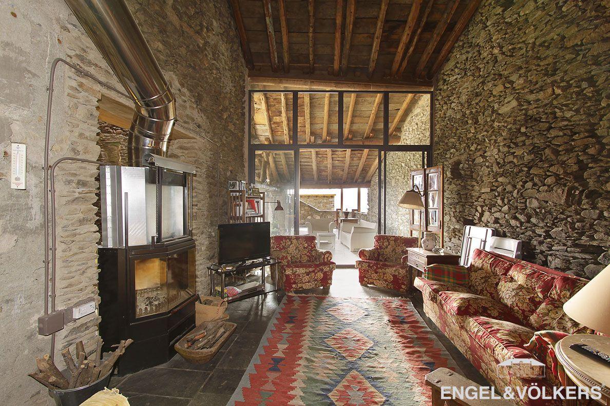 Sal n con altos techos con vigas de madera y paredes de for Decoracion de casas antiguas con techos altos
