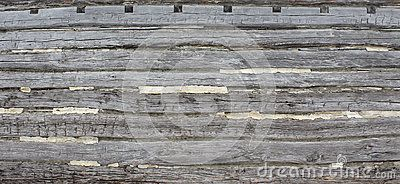 Hand hewn weathered log wall with cement chinking.