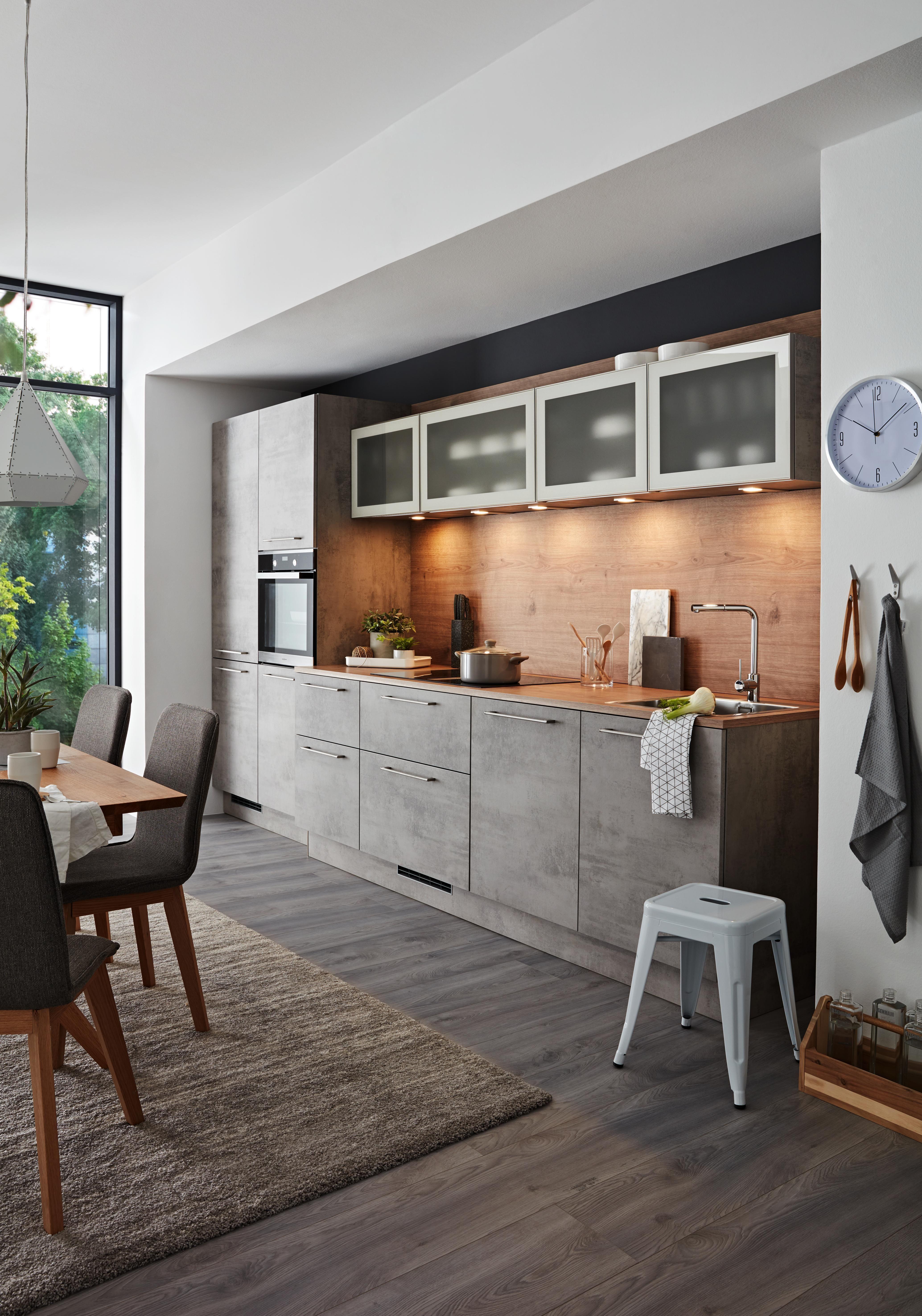 Stylische Küche in grauer Betonoptik und Arbeitsfläche aus Holz
