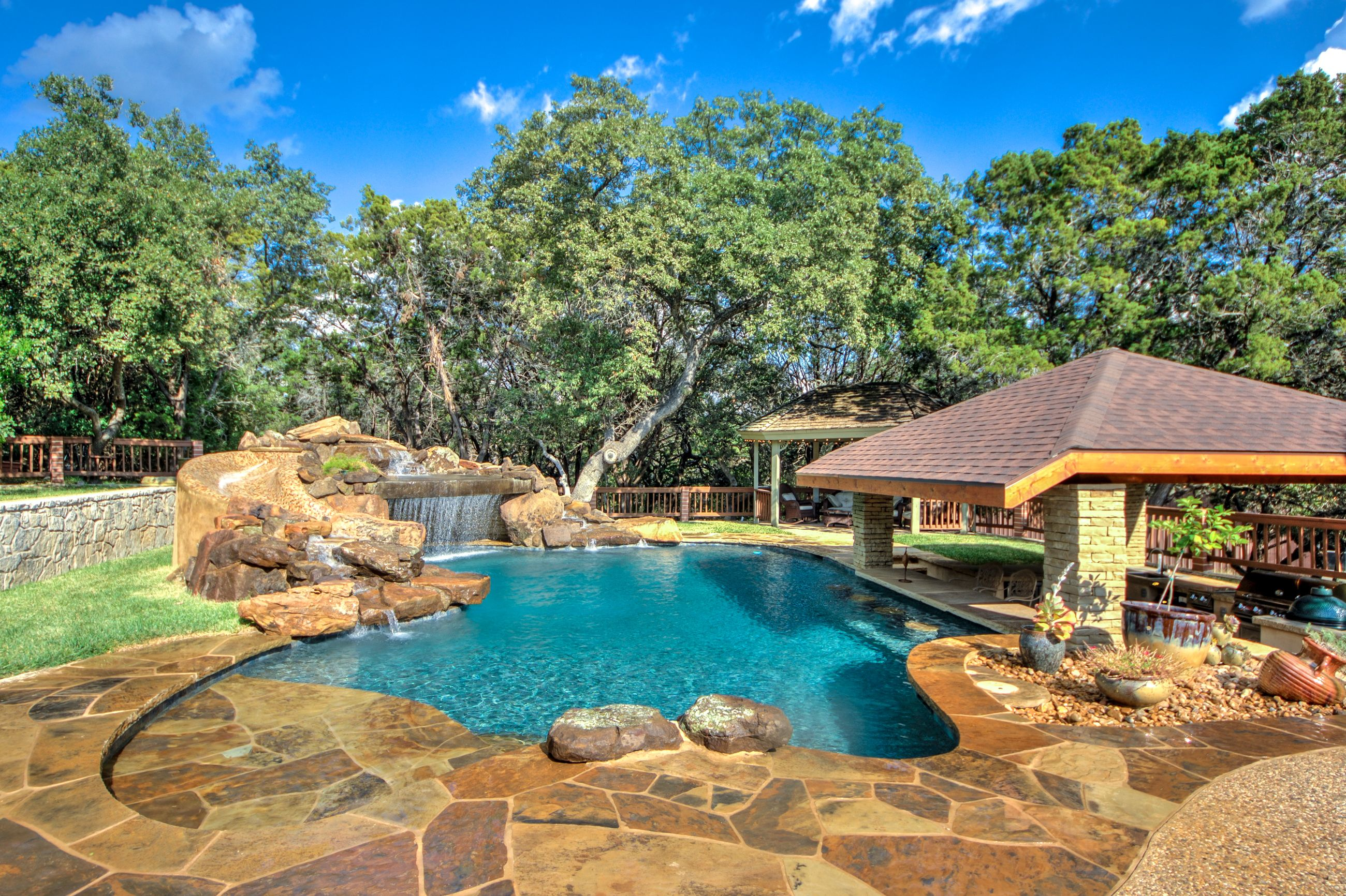 outdoor kitchen with swim up bar huge real rock waterfall with