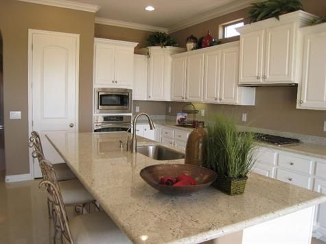 white cabinets beige walls light countertops kitchen