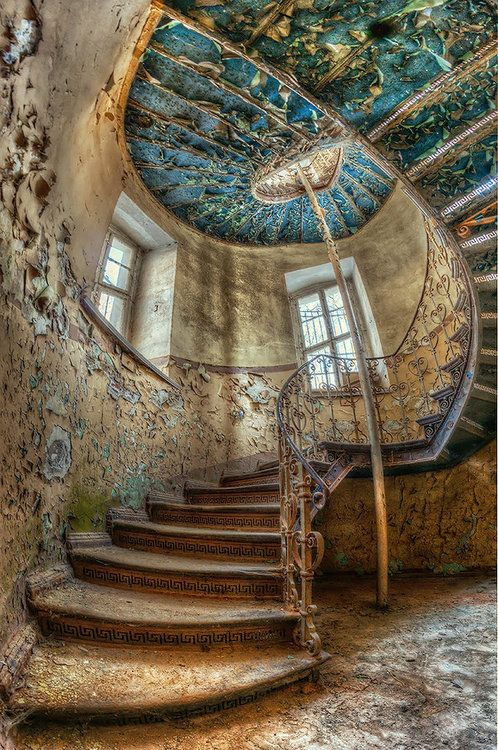 Spiral stairs. I must have been beautiful in it's day. Love the greek key risers.