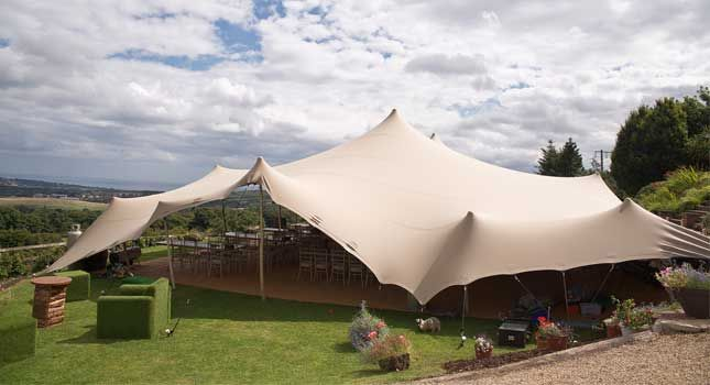 A chino-coloured stretch tent set up for an outdoor event in Ireland. & A chino-coloured stretch tent set up for an outdoor event in ...