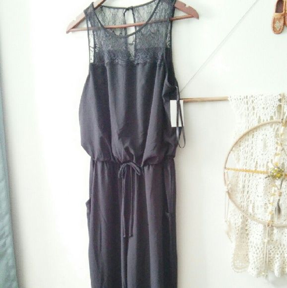 NWT Black One Piece Pant Suit This is a never worn black one piece pant suit with  lace on the upper bodice.  It has a elastic waistband, pockets and a tie front. It is a size Medium and the label is City Triangles. City Triangles Pants