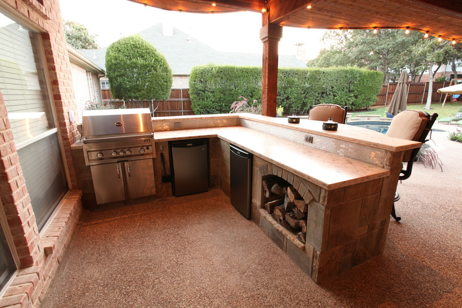 A great l shaped outdoor kitchen with storage for firewood a bar