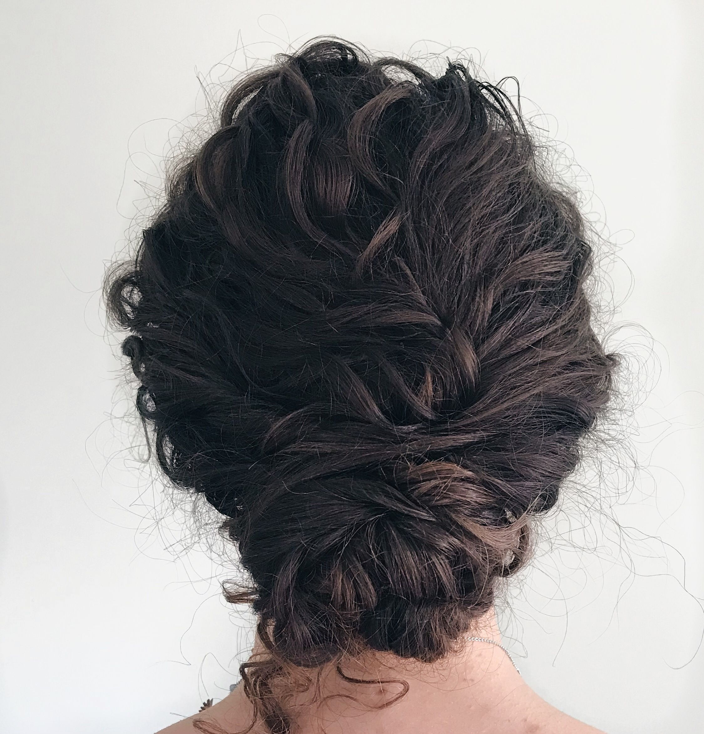 naturally curly hair in a low bun. textured hair boho style
