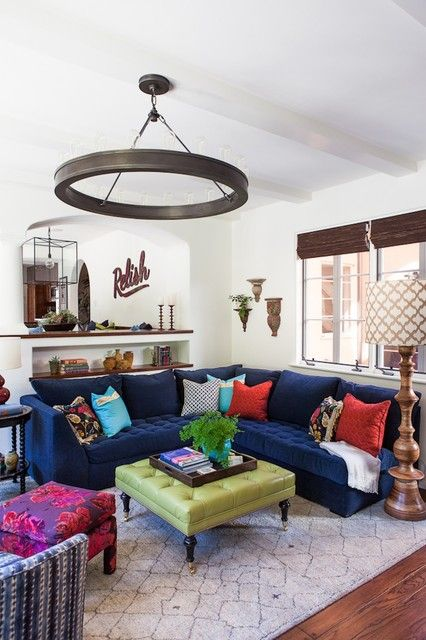 living room with round chandelier and blue blue sectional sofa also multicolor pillows with green