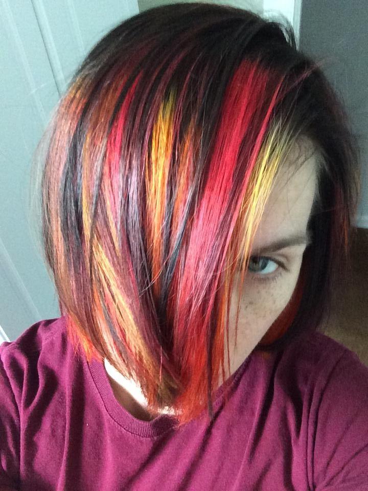 red orange and yellow streaks in dark brown hair fall