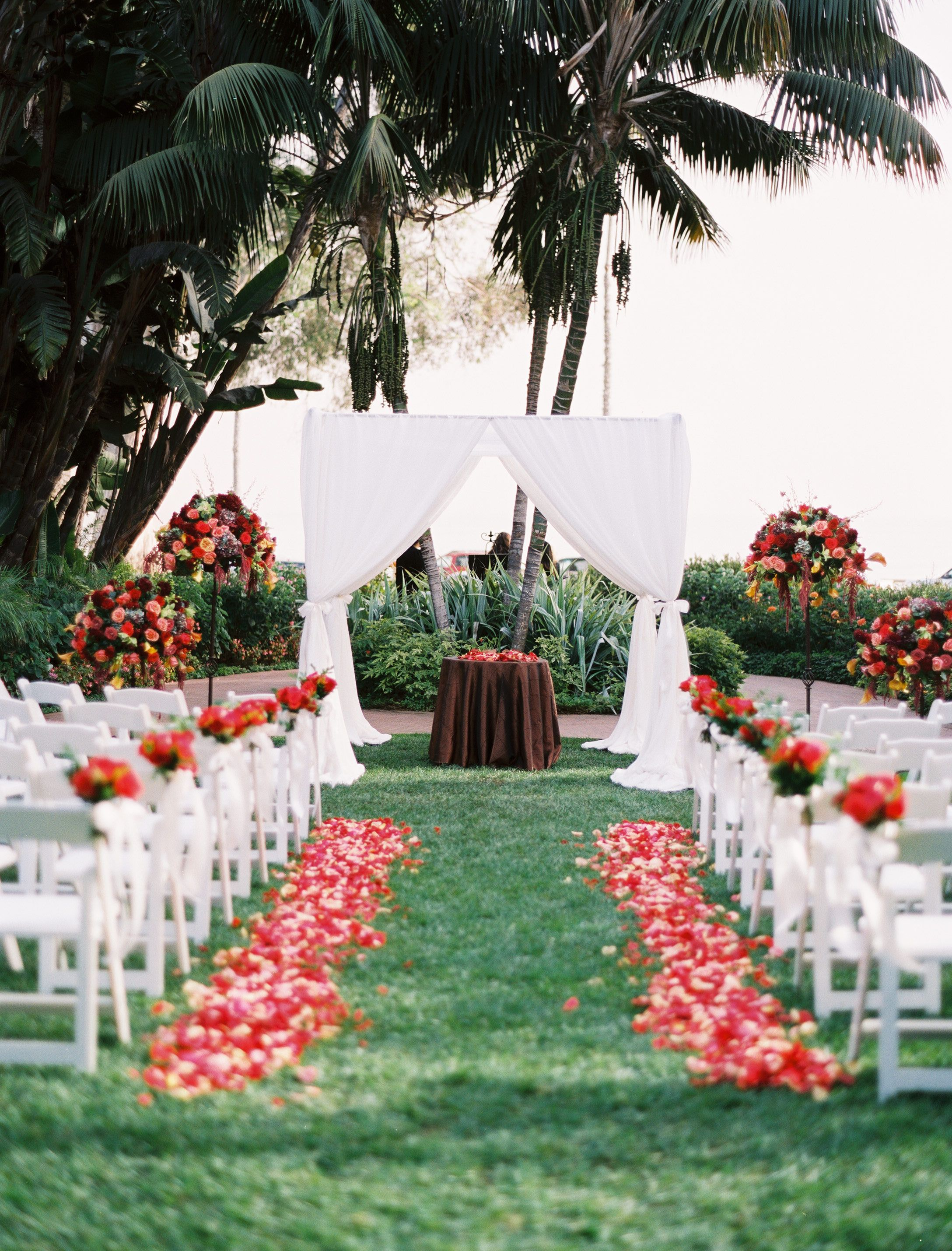 Wedding garden chairs - Bright Red Blooms And Crisp White Chairs Popped Against A Grass Aisle At This Outdoor