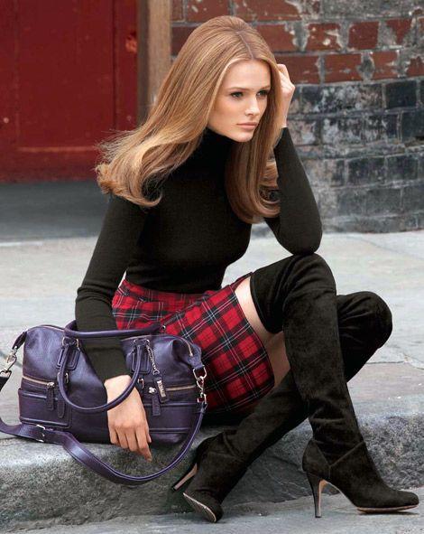 jersey de cuello alto negro, minifalda de tartán rojo, botas sobre la rodilla de ante negro, bolso tote de cuero morado para mujer