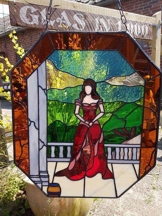 Tiffany glas in lood paneel als raamhanger van vrouw in rode jurk staande op landelijk balkon met landschap op achtergrond