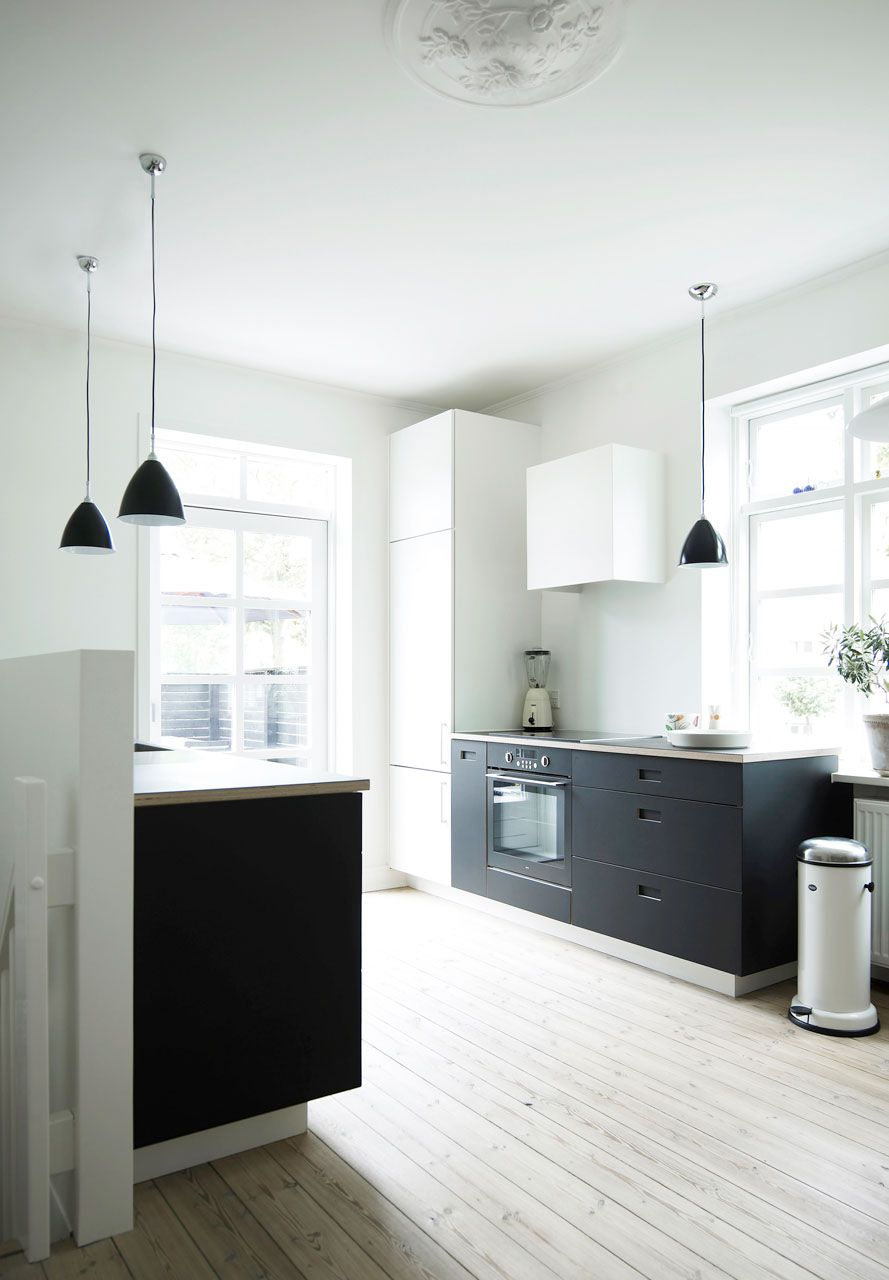 Whitewashed pickled wood floor black lower cabinets white uppers