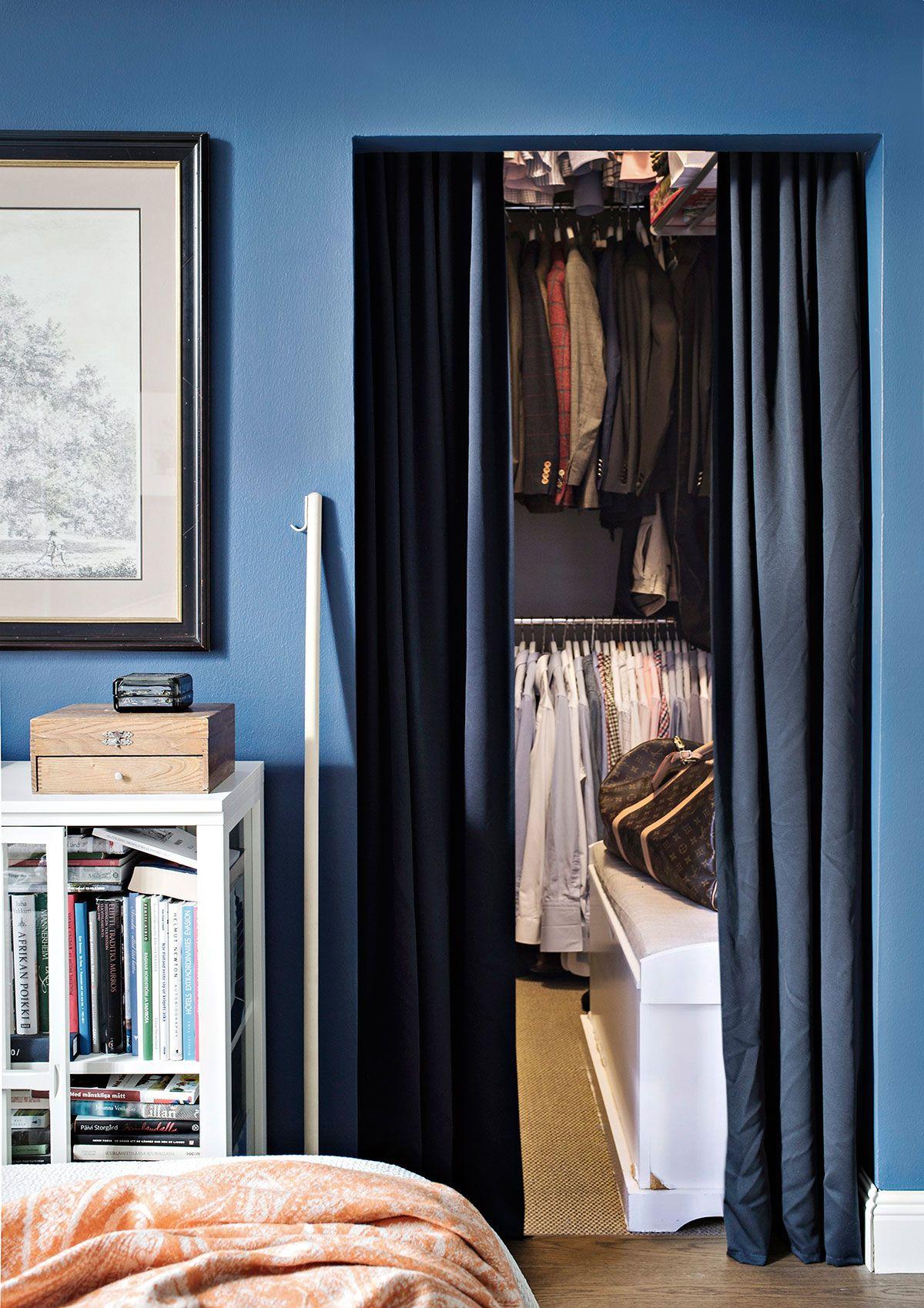 Vaatehuoneen ovena ovat paksut verhot. Pieneen tilaan on asennettu useampi tanko päällekkäin. Vaateripustimet on helppo poimia harjanvarresta ja seinäkoukusta tehdyllä kepillä.