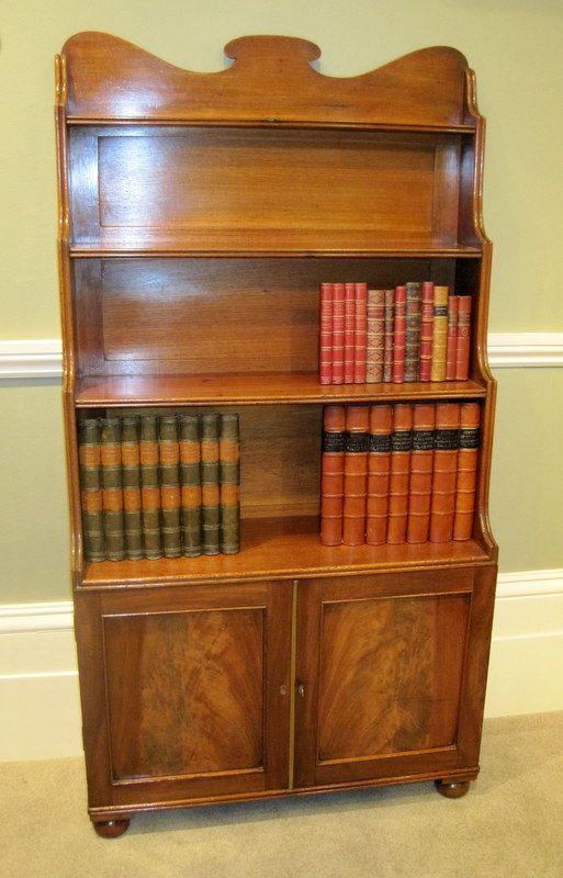 Regency Mahogany Waterfall Bookcase. Figured panel cupboard door base, and  original turned ball feet