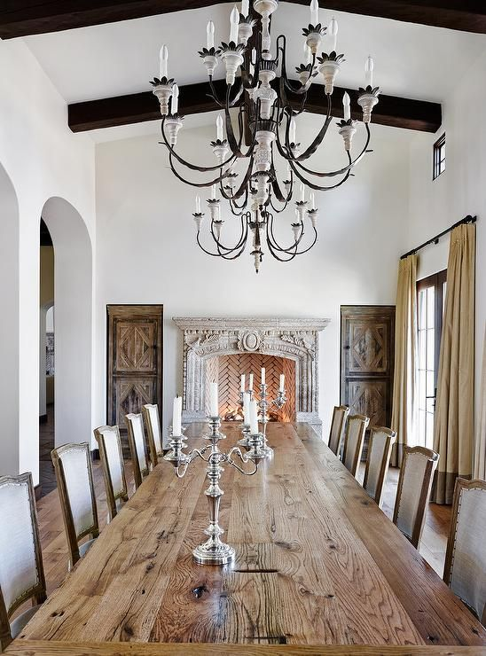 French Dining Room Features A Long Plank Table Lined With Linen Chairs Illuminated By Candle Chandeliers Placed In Front Of
