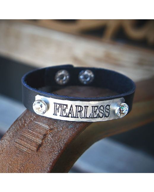 Fearless. This cuff bracelet is made with black leather. Embellished with a stamped silver plate and rhinestones.