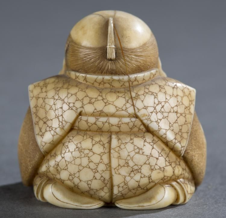 """A Japanese ivory netsuke of a seated male. Late 19th century. A seated male with chonmage hair style. Illegible tsuishu lacquer seal mark on the bottom. 1 1/2""""h. Condition: Large crack on the back."""