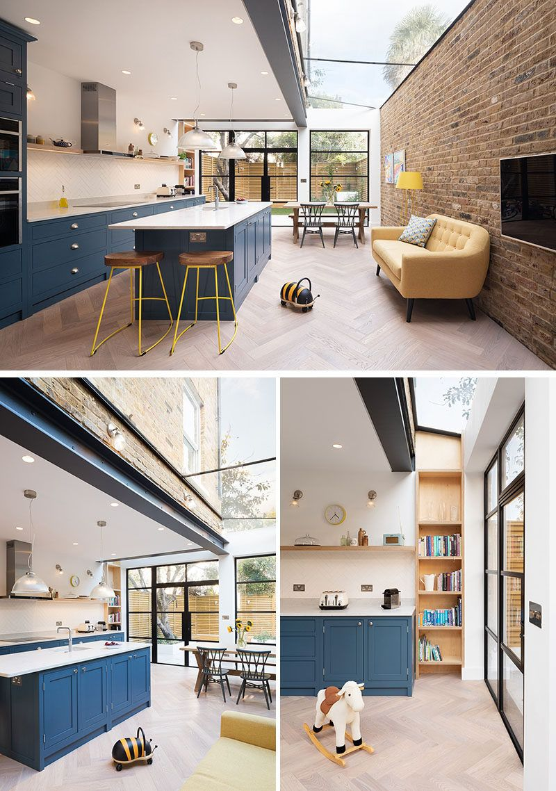 This modern extension is open plan with a new dark blue kitchen, a pastel yellow sofa that sits against a brick wall, and a dining area that has views of the backyard through the black-framed windows and doors. A skylight running the length of the extension adds an abundance of natural light to the space. #ModernHouseExtension #HouseExtension #BlueKitchen #Skylight