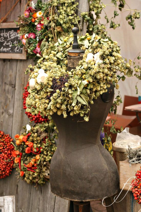 A dress form with a wreath around it's neck is a creative Xmas decoration