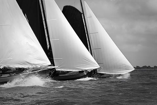 Skutsjes sailing vessels in the midst of a regatta.   Skutsje sailing race held in Holland with 14 Sk�tsjes. The sailing ships have an average age of 100 years.  Sailing vessel regatta is also known as Sk�tsjesilen.   Sailing with strong winds and dark, bad weather. Three skutsjes.  Sailing vessels shot in Black & White.