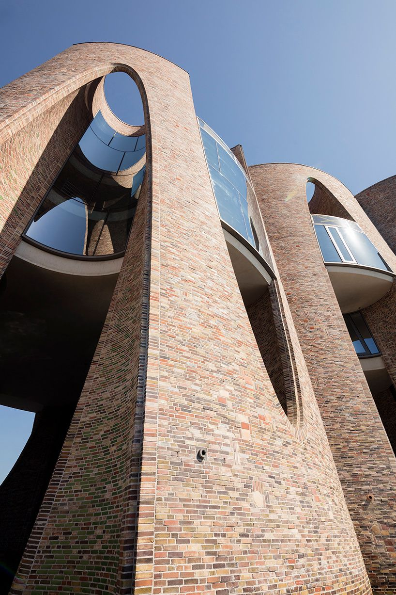 olafur eliasson s first building is a curved brick semi submerged