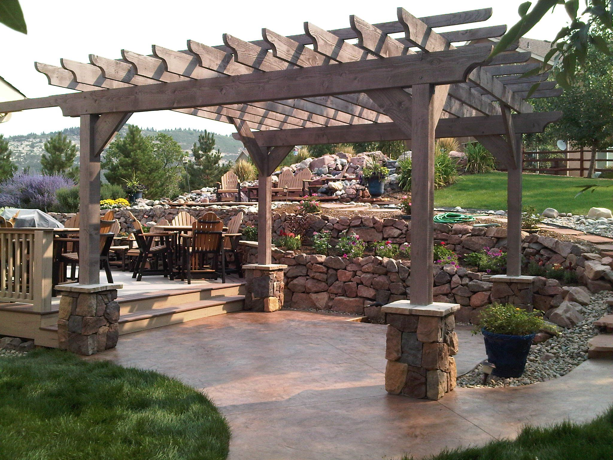 Rough sawn timber Pergola stone piers rock retaining wall stamped concrete patio
