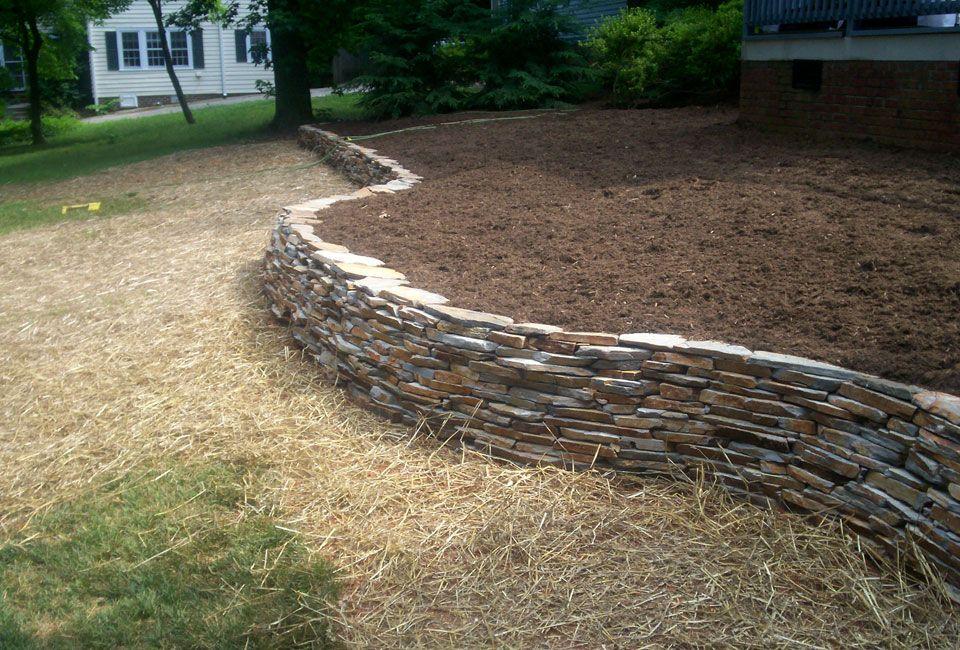 Velvet Gray Thin Veneer Dry Stack Stone Retaining Wall W Curves Aged Hardwood Mulch