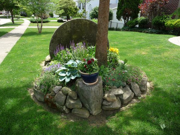 Front Yard Landscaping with Rocks | Front yard garden with stone wheel accent