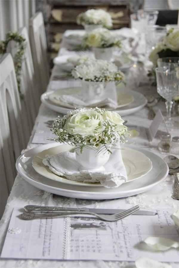 White Rose Arrangement In A Cup At Each Table Setting Is