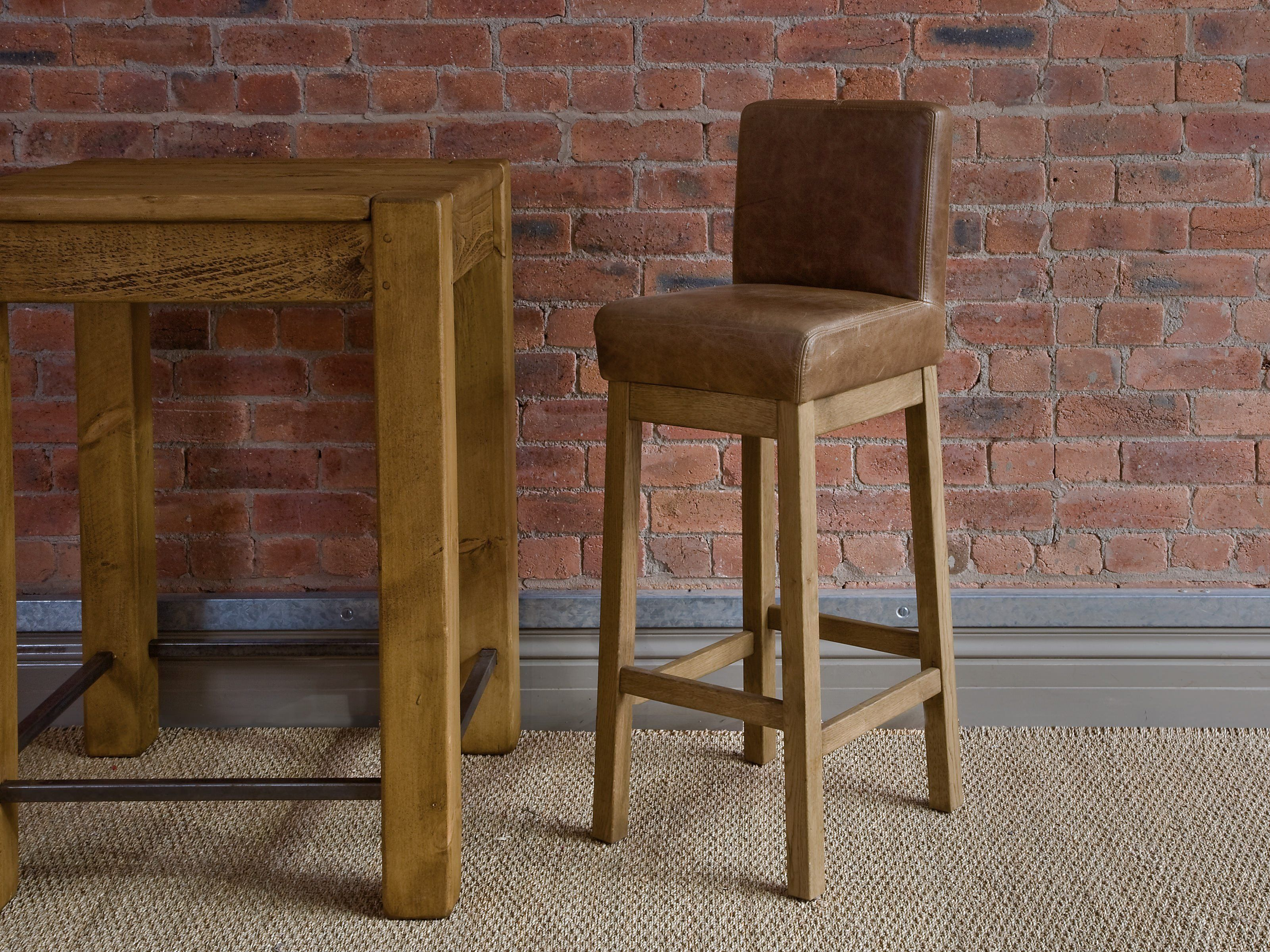Furniture Rustic Brown Suede Upholstered Bar Stool With Varnished Wooden Legs Combined Exposed Red Bricks Wall