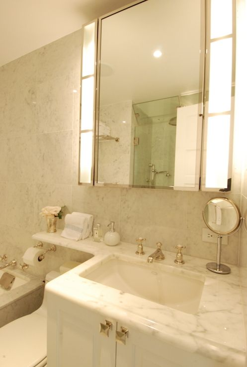 Elegant Bathroom Features Hollywood Style Vanity Mirror Over White Cabinets Topped With Marble Countertop Which